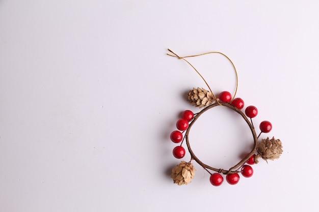 Плоская планировка деревянного рождественского украшения с небольшими сосновыми шишками, изолированными на белом