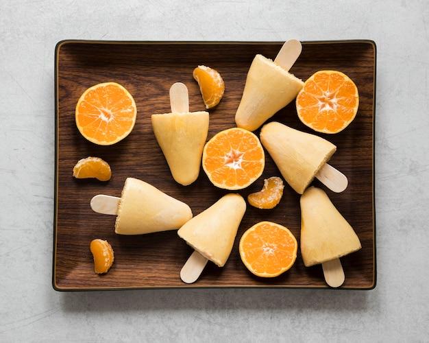 おいしいオレンジ風味のアイスキャンディーのフラットレイ