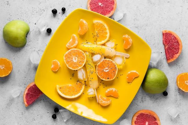 フルーツと氷のおいしいアイスキャンディーのフラットレイ
