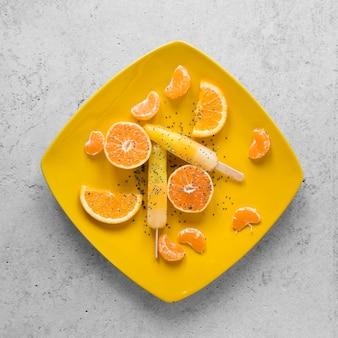 オレンジとおいしいアイスキャンディーのフラットレイ