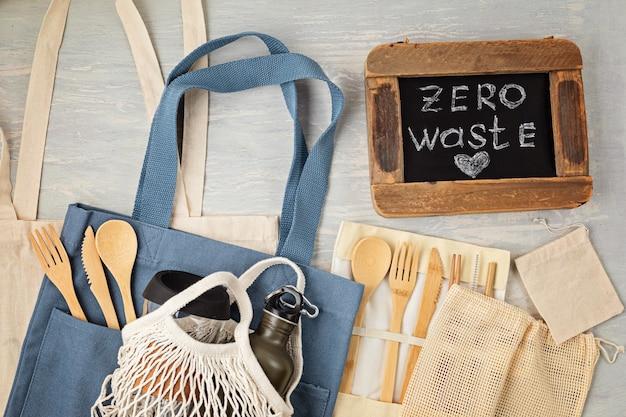 제로 폐기물 키트의 평평한 누워. 친환경 대나무 칼 붙이, 메쉬 면봉, 재사용 가능한 커피 텀블러, 브러쉬 및 물병 세트. 지속 가능하고 윤리적이며 플라스틱이없는 라이프 스타일. 평면도