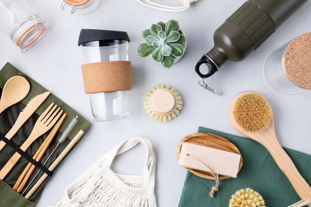 제로 폐기물 키트의 평평한 누워. 친환경 대나무 칼 붙이, 메쉬 면봉, 재사용 가능한 커피 텀블러, 브러쉬, 바 비누, 물병 세트. 지속 가능하고 윤리적이며 플라스틱이없는 라이프 스타일
