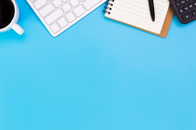青いテーブルの上のノートパソコンと現代の職場のフラットレイアウトオフィスデスクテーブル