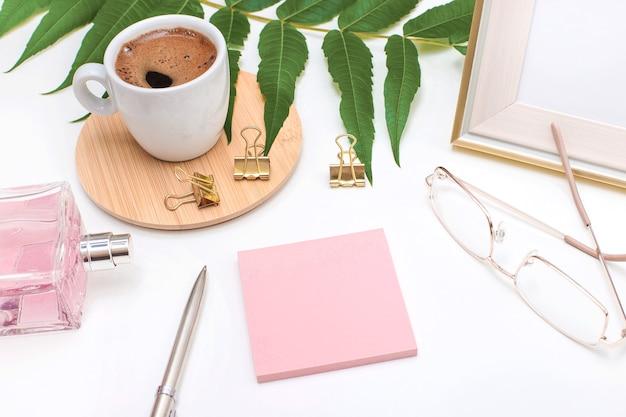 フラットレイ、オフィスデスク、上面図。コーヒーマグ、怒っている植物の葉、香水瓶、金のグラスとペン、白い背景のテキスト用のピンクのステッカーが付いたワークスペース。女性ホームオフィス