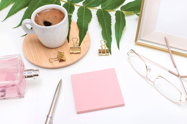 Flat lay, office desk, top view. workspace with a coffee mug, an angry plant leaf, a perfume bottle, gold glasses and a pen, and a pink sticker for text on a white background. woman home office