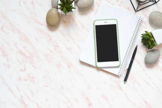 Flat lay office marble desk with phone, stones and succulents