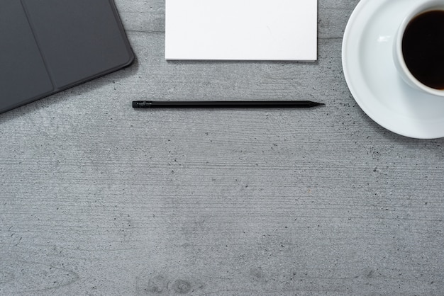 Flat lay of the office space with a view of a tablet with a gray case