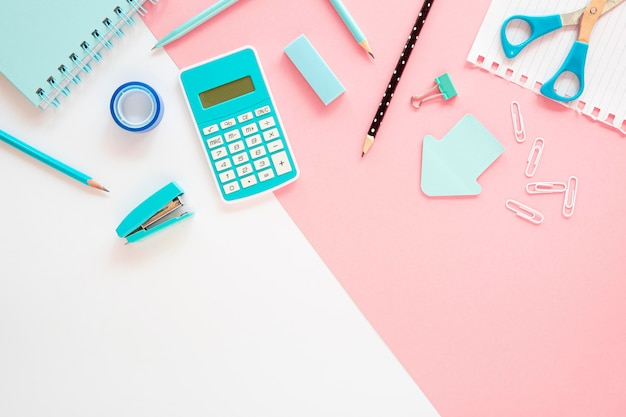 Flat lay of office stationery with calculator and stapler