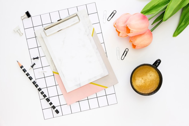 Flat lay of office stationery with coffee and tulips