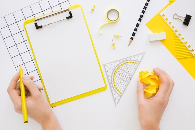 Flat lay of office stationery with hands and notepad