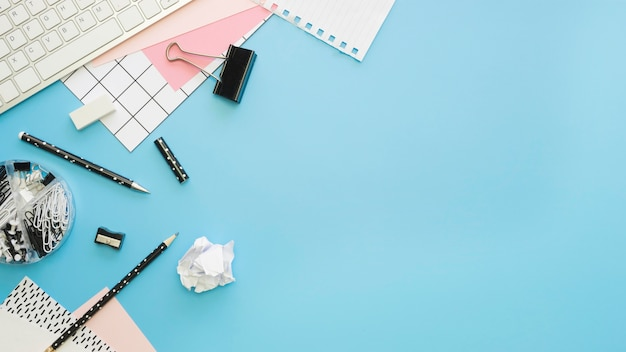 Flat lay of office stationery with keyboard and pencils