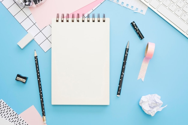 Flat lay of office stationery with notebook and tape