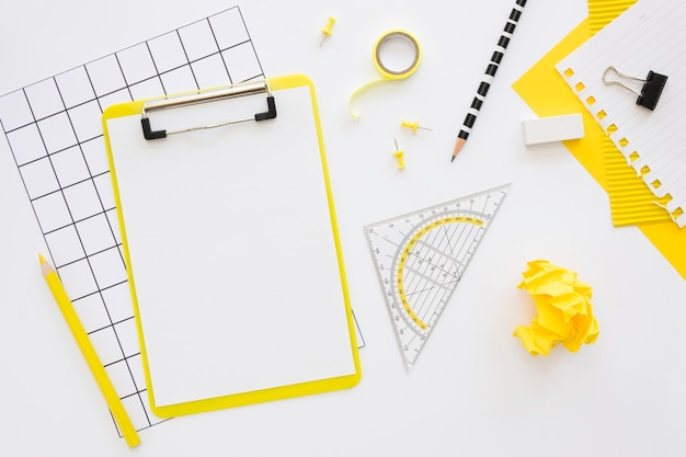 Flat lay of office stationery with notepad and crumpled paper