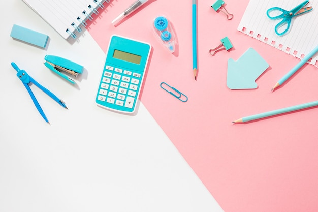 Flat lay of office stationery with stapler and calculator