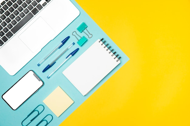 Flat lay office supplies with colourful background