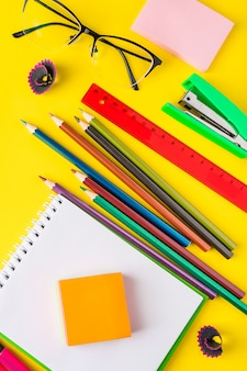 Flat lay of office supplies on yellow background.
