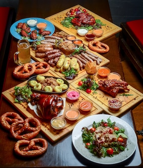 Flat-lay of oktoberfest dinner table with grilled meat sausages, pretzel pastry, potatoes, cucumber salad, sauces, beers
