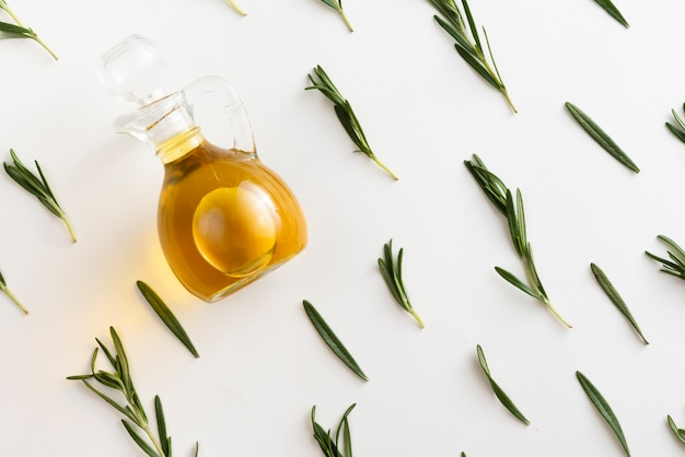 Flat lay olive oil in a bottle with leaves