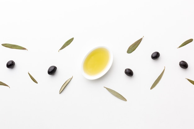 Flat lay olive oil in saucer with leaves and black olives