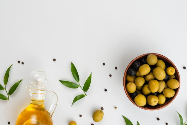 Flat lay olives in bowl and oil bottle