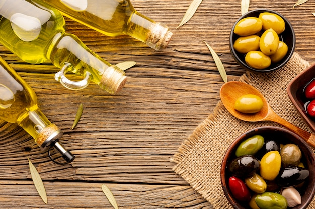 Flat lay olives in bowls oil bottles and leaves on textile material