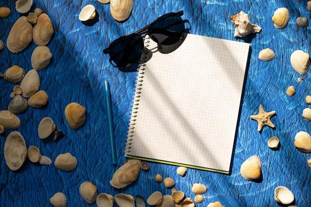 平らな青い背景の空白のノートブックのコピースペースに横たわっていた。夏の計画のコンセプト