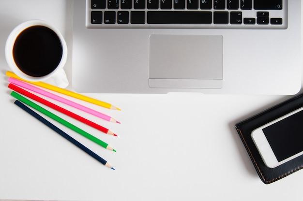 フラットは、ラップトップコンピューター、携帯電話のガジェット、消耗品、ブラックコーヒーと白い木製のワークスペースに横たわっていた。