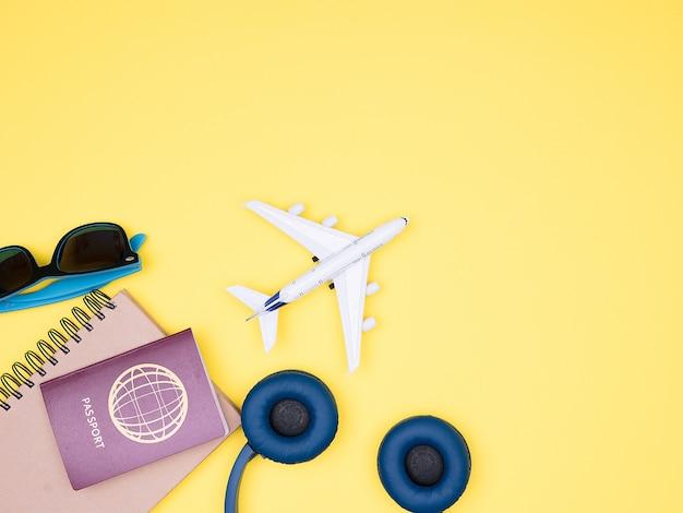 비행기, 헤드폰, 여권, 선글라스의 노란색 배경에 평평하게 놓여 있습니다. 복사 공간 사용 가능