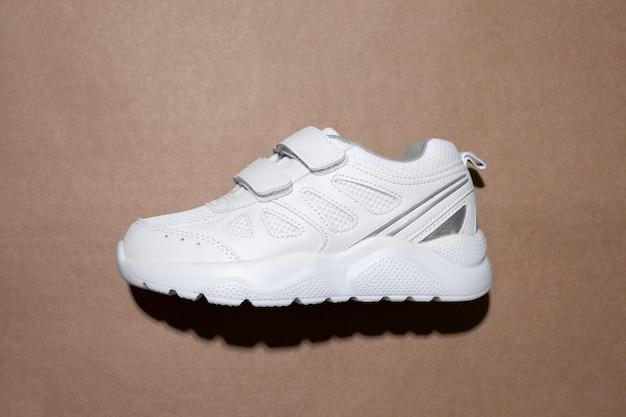 벨크로 패스너가 있는 플랫 레이 1개의 흰색 어린이 운동화로 중앙 측면에 쉽게 미끄러짐...
