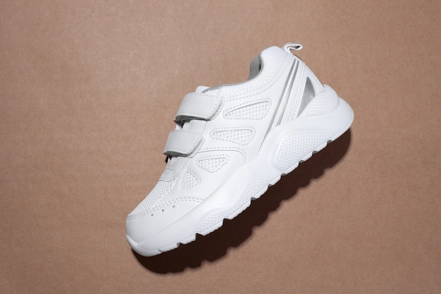 Flat lay one white kid sneakers with velcro fasteners on the side with hard shadows in the center is...