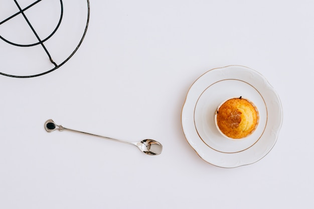 Flat lay orange muffins on a metal stand and plate