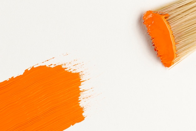 Flat lay of orange paint stroke and brush
