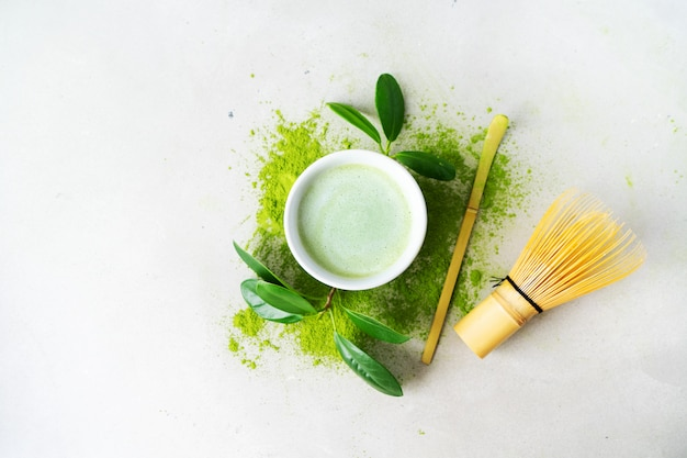 Flat lay of organic green tea matcha powder with japanese tools chasen bamboo whisk