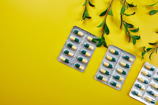 Flat lay organic medical pills, capsules in blisters with green leaf, herbal plant on a yellow background