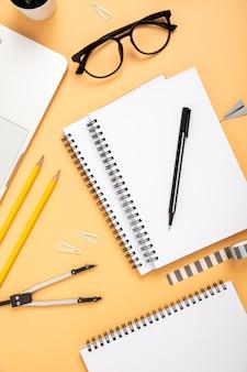 Flat lay organised arrangement of desk elements on orange background