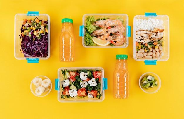 Disposizione piana di contenitori per alimenti in plastica organizzata con pasti e bottiglie di succo d'arancia