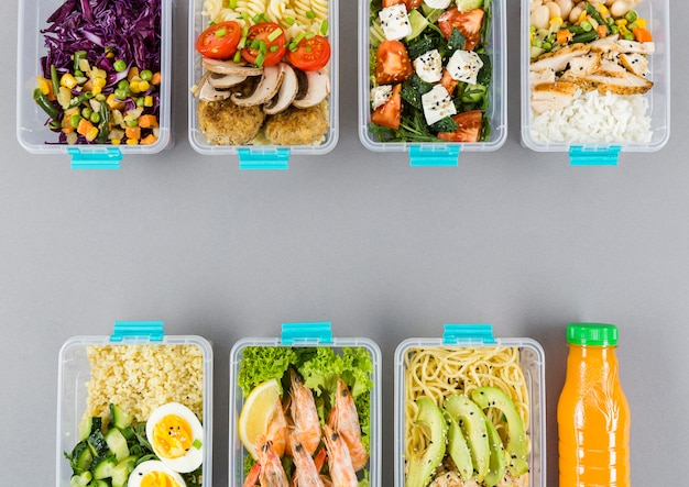 Flat lay of organized plastic food containers with meals