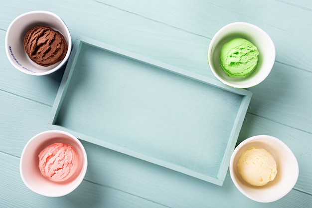 Flat lay, overhead shoot of homemade assorted ice cream on light blue wooden surface. healthy summer food concept. top view, copy space