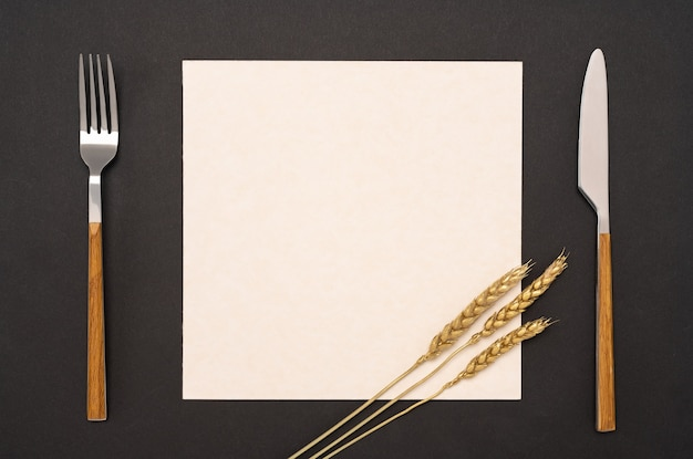 Flat lay overhead view blank recipe paper. blank card and cutlery on black table