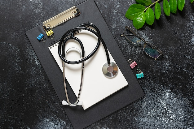 Flat lay overhead view of doctor's office table with blank notepad, stethoscope, glasses and green plant on dark rustic table.