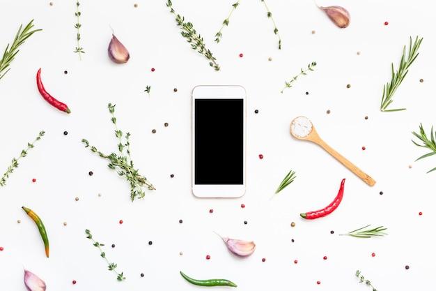 평면 레이아웃 스마트폰은 녹색 허브와 향신료가 있는 흰색 배경에 빈 텍스트 공간을 흉내냅니다. 메뉴 디자인 음식 블로그 레시피 요리책 또는 요리 재료가 포함된 배달 앱