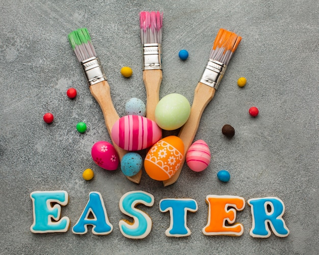 Flat lay of paint brushes with colorful easter eggs