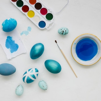 Flat lay of painted easter eggs with designs and palette