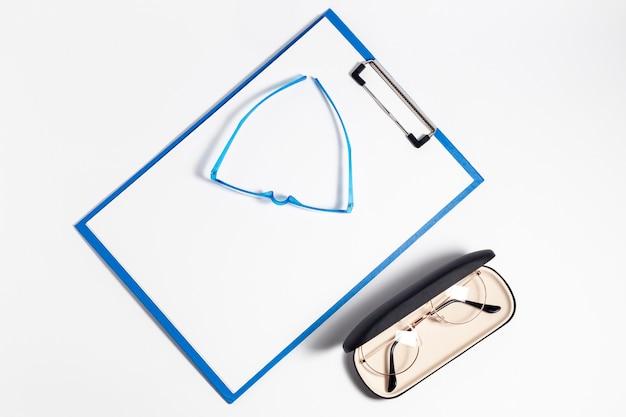 Disposizione piatta di un paio di occhiali in custodia e blocco note