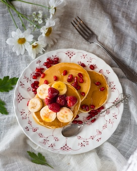 Flat lay pancake tower with banana and raspberries