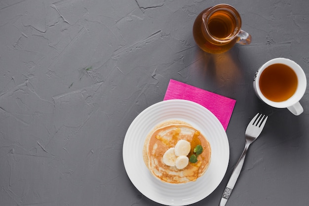 Flat lay pancakes with tea and copy space