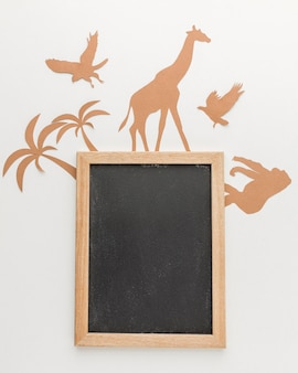 Flat lay of paper animals with blackboard for animal day