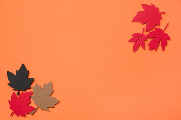 Flat lay paper autumn leaves arrangement on orange background with copy space