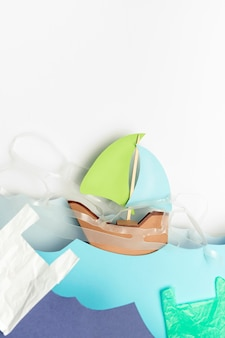 Flat lay of paper boat with plastic and bags