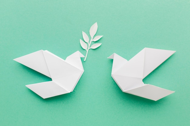 Flat lay of paper doves with leaves